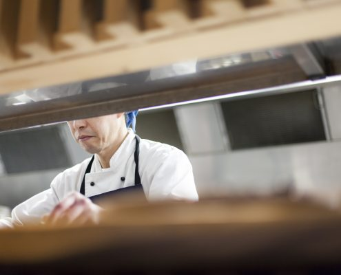A chef working at Cocoro restaurant with Ora King Salmon